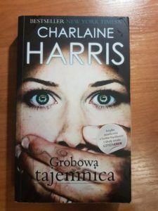 """Na zdjęciu oryginalna okładka książki """"Grobowa tajemnica"""" przedstawiająca przerażoną twarz kobiety i męską dłoń zasłaniającą jej usta."""