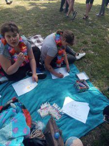 Dwie dziewczynki siedzą na niebieskim kocu. Na kartkach papieru rozwiązują zagadki. Jedna z dziewczynek ma namalowane czarne piegi. Na szyjach mają zarzucone sznurki z kolorowymi sztucznymi kwiatami. Na kocu leżą kolorowe pisaki, pudełko z kredkami i kartki do kolorowania.
